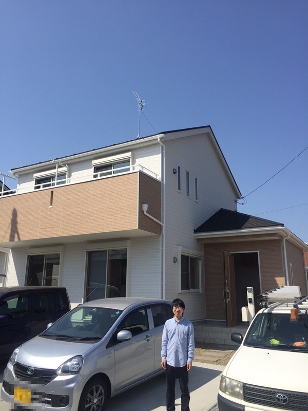 お家の正面に立つご主人様。屋根上にはテレビのアンテナが見える。